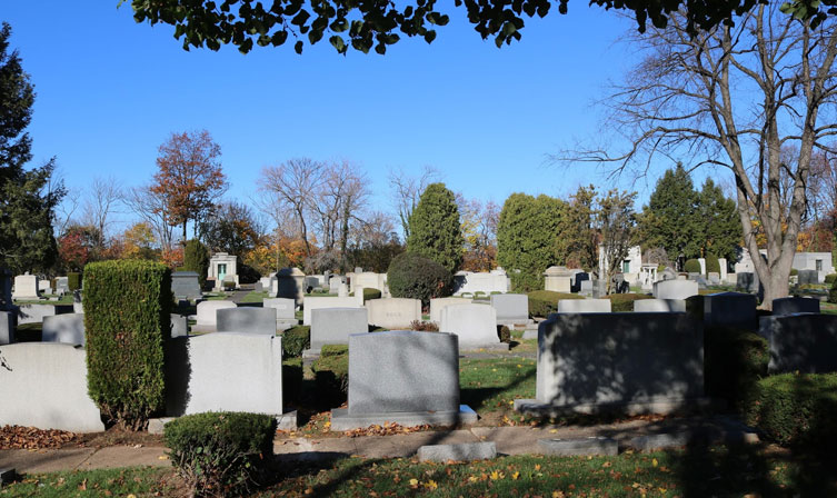Row of headstones with one tilted
